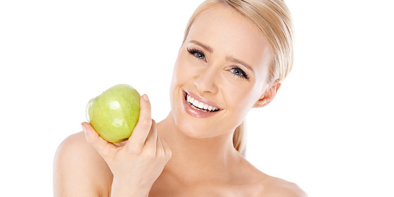 Adorable and healthy woman holding apple